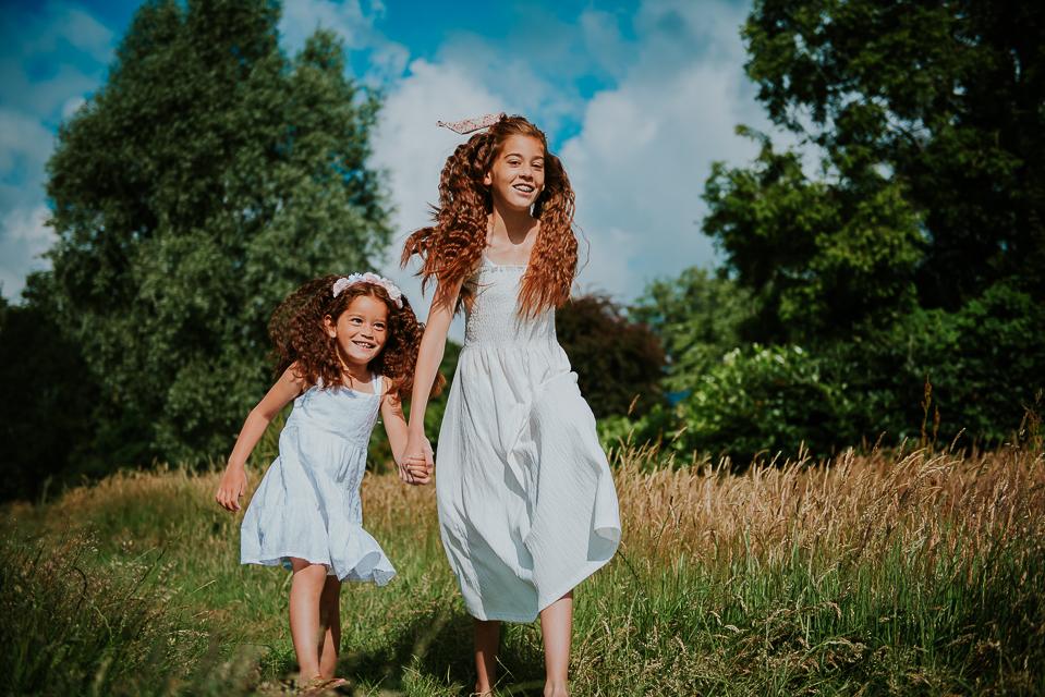 Huppelende zusjes met witte jurkjes in de natuur. door fotograaf Nickie Fotografie uit Dokkum, Friesland