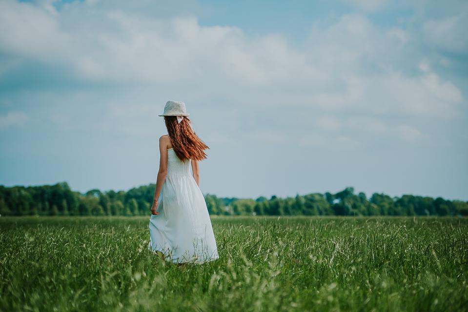 Meisje in wit jurkje en wit hoedje dwalend door de weilanden door fotograaf Nickie Fotografie uit Dokkum, Friesland