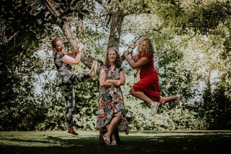 Geinige portret van drie zussen in een appelgaard door portretfotograaf Nickie Fotografie uit Dokkum, Friesland