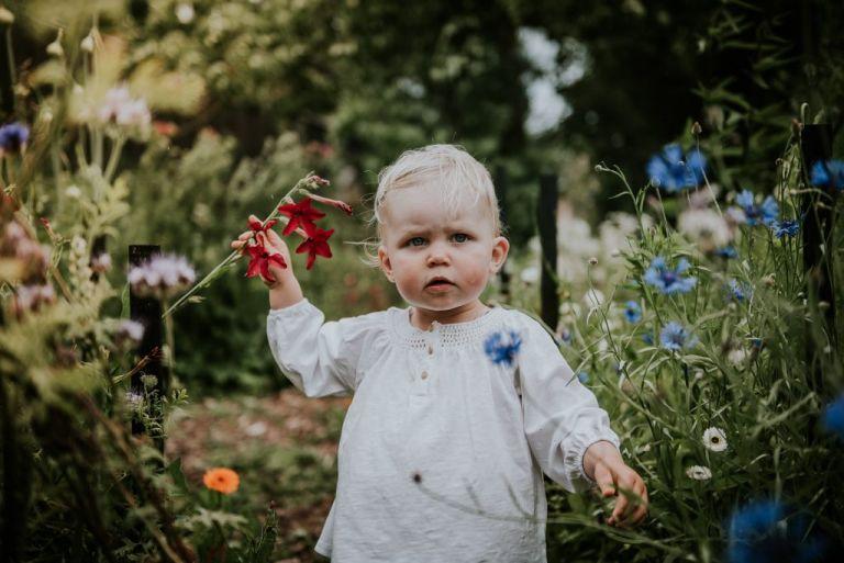 Klein meisje onder de indruk van de prachtige bloementuin. Kinderportret door portretfotograaf Nickie Fotografie uit Dokkum, Friesland
