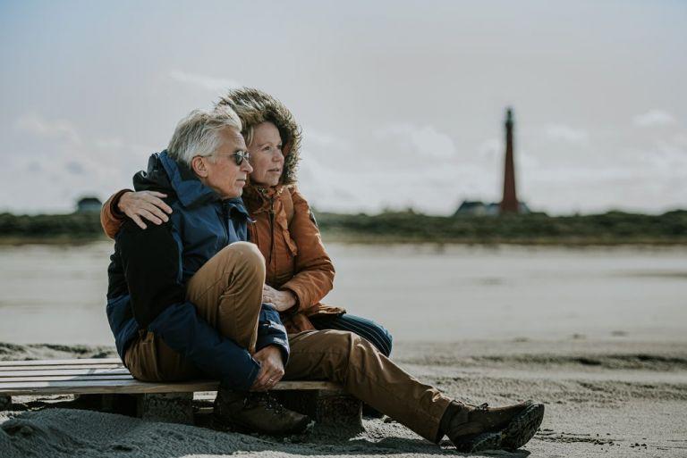 Zittend op het strand van Schiermonnikoog met op de achtergrond de rode vuurtoren. Lekker genieten en uitkijkend over de zee. Fotoshoot door fotograaf Nickie Fotografie uit Dokkum