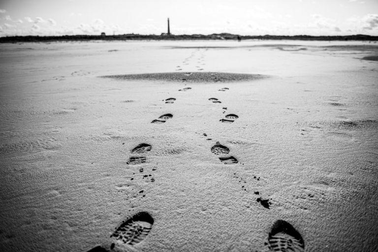 Zwart/wit foto van voetstappen op het strand naar de vuurtoren toe van Schiermonnikoog. Fotoreportage door fotograaf Nickie Fotografie