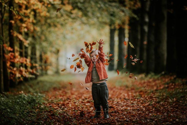 Herfstshoot Friesland, driesumer bos. Peuter speelt met herfstbladeren. Fotosessie door fotograaf Nickie Fotografie