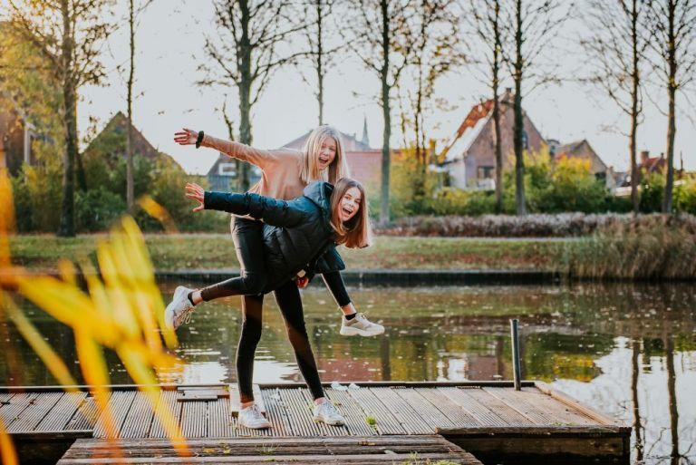 Twee tieners lekker gek aan het doen in het gouden uur. Tienershoot door fotograaf Nickie Fotografie uit Dokkum, Friesland