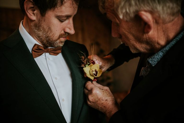 Bruidegom krijgt bloemcorsage opgespeld. Bruidsfotografie Friesland door bruidsfotograaf Nickie Fotografie uit Dokkum